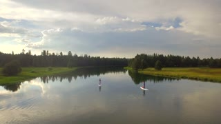 Paddle boarders ride on Oregon lake next to green forest and sunset sky 3