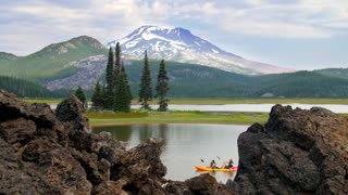 People kayak by Oregon mountainside under blue sky 2