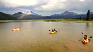 People kayak on lake next to Oregon mountainside under gorgeous sky
