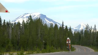 People ride bicycles past green forest and gorgeous mountainside 2