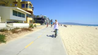People ride bikes alongside beach homes and beach on sunny day 2