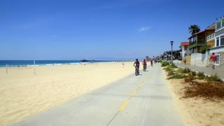 People ride bikes alongside beach homes and beach on sunny day 6
