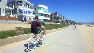 People ride bikes alongside beach homes and beach on sunny day