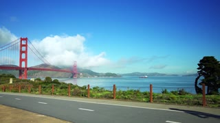 People ride bikes on road near Golden Gate Bridge and San Francisco bay 3