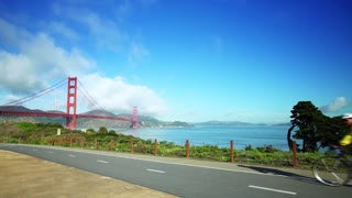 People ride bikes on road near Golden Gate Bridge and San Francisco bay 6