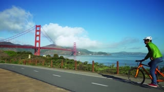 People ride bikes on road near Golden Gate Bridge and San Francisco bay 7