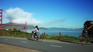 People ride bikes on road near Golden Gate Bridge and San Francisco bay 8