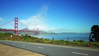 People ride bikes on road near Golden Gate Bridge and San Francisco bay