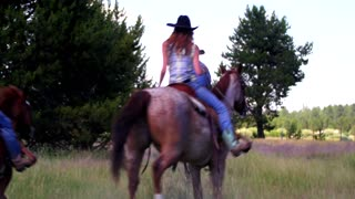 People ride horses in cowboy hats through green field