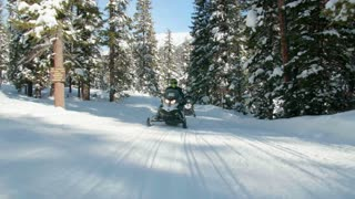 People ride snowmobiles through snow covered woods 2