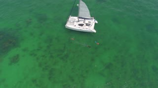 People snorkel by sailboat in clear ocean 2