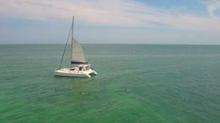People snorkel by sailboat in clear ocean 3
