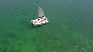 People snorkel by sailboat in clear ocean 4