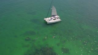 People snorkel by sailboat in clear ocean 5
