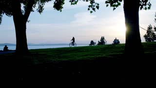 Person rides a bike through a park during sunset 3