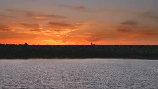 Person walks across rock wall and beautiful sunset horizon