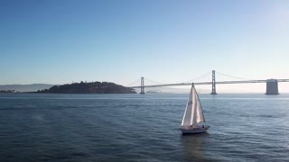 Sailboat crosses water by Oakland Bay bridge under blue sky