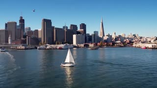 Sailboat crosses water by San Francisco skyline 2