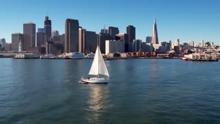 Sailboat crosses water by San Francisco skyline 3