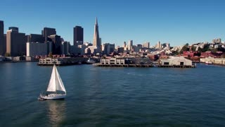 Sailboat crosses water by San Francisco skyline 7