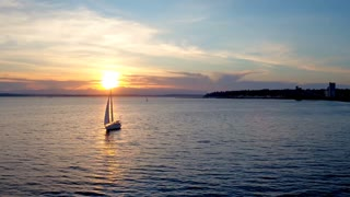 Sailboat floats in water by beautiful sunset 2