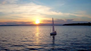 Sailboat floats in water by beautiful sunset 4