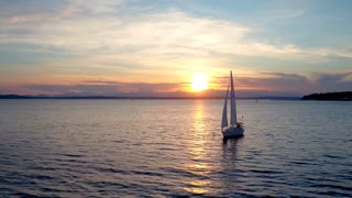 Sailboat floats in water by beautiful sunset