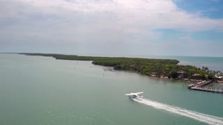 Sea plane takes off across tropical ocean