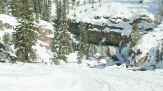 Snowmobiles drive by a beautiful waterfall 2