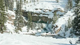 Snowmobiles drive by a beautiful waterfall