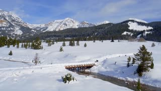 Snowmobiles drive over bridge with majestic background 3
