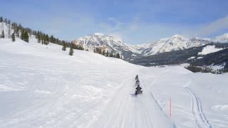 Snowmobiles race through trail by beautiful mountains 2