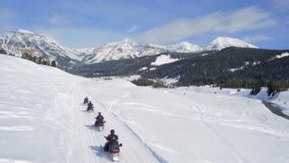 Snowmobiles race through trail by beautiful mountains 3