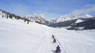 Snowmobiles race through trail by beautiful mountains 4