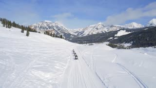 Snowmobiles ride to snow covered mountains under blue sky