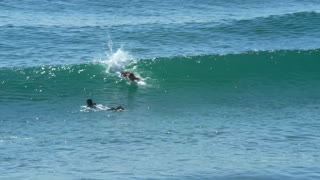 Surfer catches and rides wave while other surfers watch 4