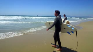 Surfers walk into ocean with surfboards on sunny day