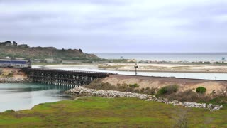 Train rides by California beach and horizon