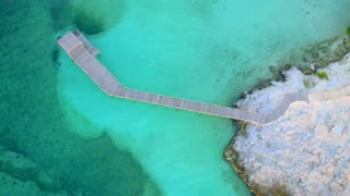 Tropical Dock over Rocks in Paradise from Aerial Drone 2