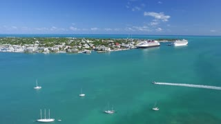 Boat Passing in Front of Tropical Town with Cruise Ships