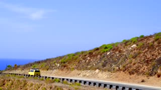 Classic VW Bus Driving Along the Coast
