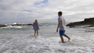 Couple in the Shallow Water at the Beach