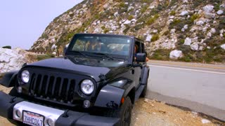 Couple Looks out Jeep at Big Sur
