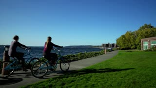 Couple Rides Bikes by Seattle Waterfront Tracking Shot