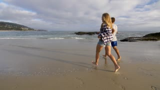 Couple Runs to the Water on the Beach