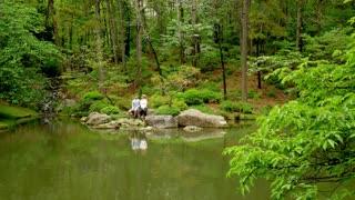 Couple Sitting at Beautiful Pond, Chatting, Slow-Motion