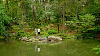 Couple Standing Across Beautiful Pond, Pointing, Slow-Motion