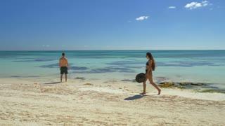 Couple Walking On White Sand Beach