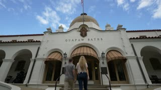 Couple Walks Into Historic Bath House Entrance, Slow Motion Low Shot