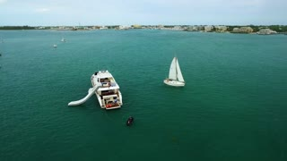 Crew on Anchored Yacht and Smaller Sailboat